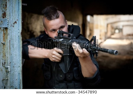 Aiming man with M4 rifle on the ruined building background. Focus point on the face. - stock photo