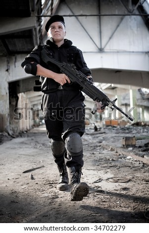 Aiming man with the machine gun on the ruined building background. - stock photo