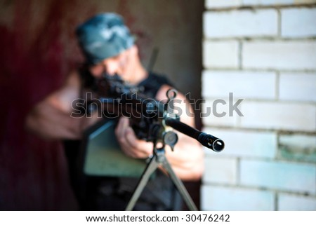 Aiming mercenary with light submachine gun on the brick wall background.