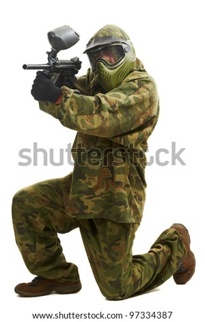 Aiming paintball sport player man in protective camouflage uniform and mask with marker gun over white background - stock photo