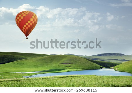 Air balloon flying over the meadows with lake - stock photo