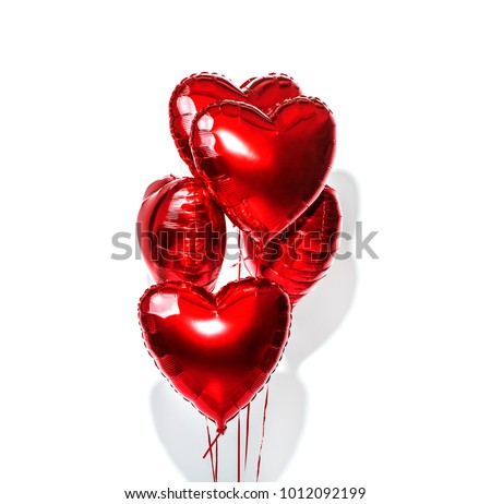 Air Balloons. Bunch of red heart shaped foil balloons isolated on white background. Love. Holiday celebration. Valentine's Day party decoration. Metallic heart shape balloons