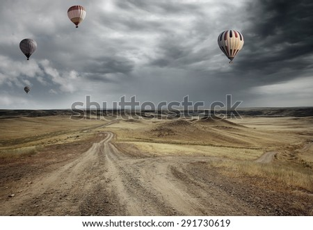 Air balloons flying over the country road - stock photo