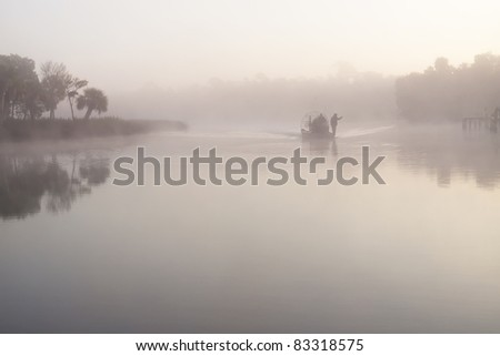 Air boat coming out of the mist at dawn - stock photo