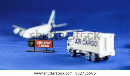 Air Cargo truck heading Runway Ahead sign and defocusing silhouette of an airplane - toy models - stock photo