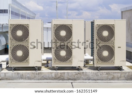 Air compressors on roof of factory with blue sky background. - stock photo