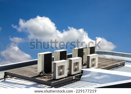 air condition outdoor unit, on the roof with blue sky - stock photo