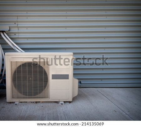 air conditioneer on the corrugated metal wall - stock photo