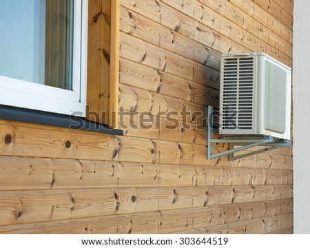 Air conditioner condenser on the wooden wall of boards. - stock photo