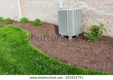 Air conditioner condenser unit standing outdoors in a garden in a neat clean mulched flowerbed for easy access for maintenance