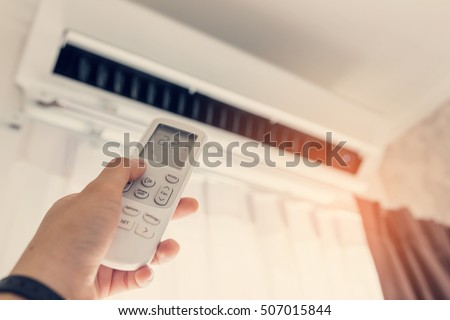 air conditioner inside room woman operating stock photo. Black Bedroom Furniture Sets. Home Design Ideas