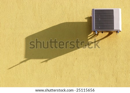 Air conditioner on yellow wall with shadow - stock photo