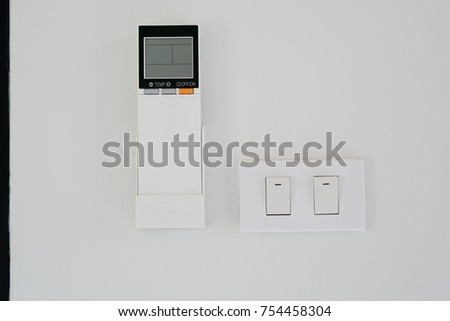 Air Conditioner Remote Controller And Light Switches At A White Painting  Concrete Wall