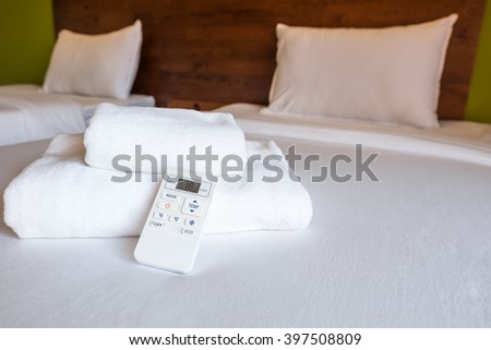 Air conditioner remote, towel and white pillows in bed. - stock photo