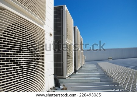 Air Conditioner units (HVAC) on the roof of an industrial building. Blue sky in the background. No people. Copy space. - stock photo