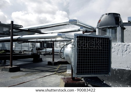 Air-conditioning and heat ducts on a modern building roof. Useful file for your company specialized in heating and air-conditioning systems. - stock photo