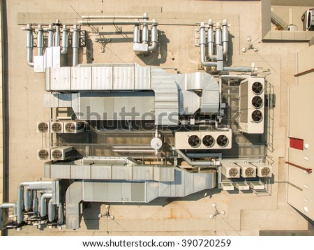 Air conditioning equipment atop a modern building - aerial/drone view of the roof with all the necessary installations - stock photo