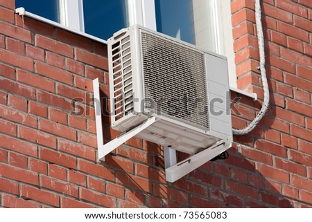 Air conditioning heat pump mounted on brick wall. - stock photo