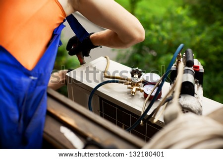 Air conditioning master preparing to install new air conditioner. drilling the wall. - stock photo