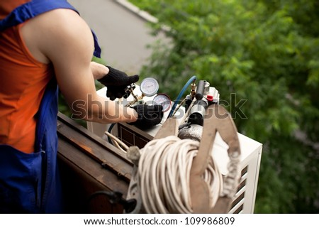 Air conditioning master preparing to install new air conditioner. removal of gases from the freon tubes - stock photo