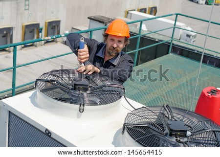 Air Conditioning Repair, repairman on the roof fixing huge air conditioning system. Model is actual electrician.  - stock photo
