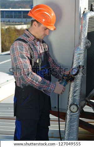 Air Conditioning Repair, Young repairman on the roof fixing air conditioning system - stock photo