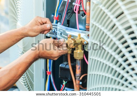 Air Conditioning Technician and A part of preparing to install new air conditioner.  - stock photo