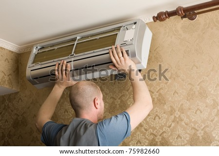 Air conditioning technician installs a new air conditioner in the apartment. - stock photo