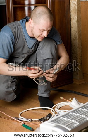 Air conditioning technician prepares a new air conditioner to be installed in the apartment. - stock photo