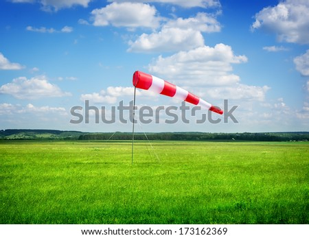 Air field direction sign and a wind force against the dark blue sky - stock photo