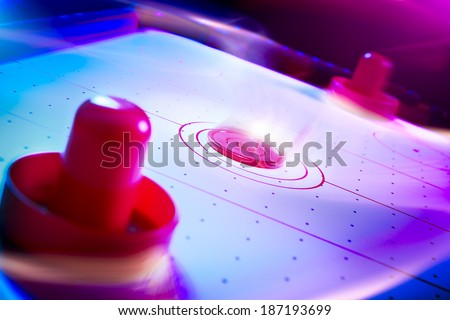 Air hockey table with dramatic lighting and motion trails - stock photo