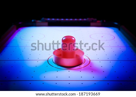 Air hockey table with dramatic lighting on a dark background - stock photo