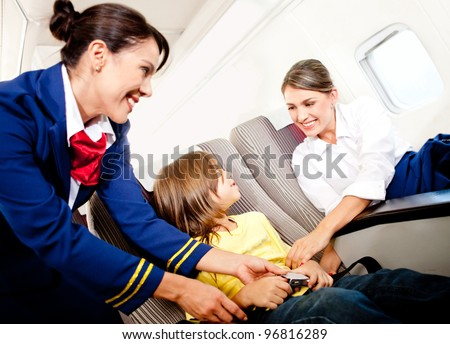 Air hostess helping a kid to fasten his seatbelt - stock photo