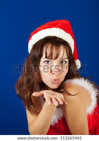 Air-kissing   girl in christmas costume over blue background - stock photo
