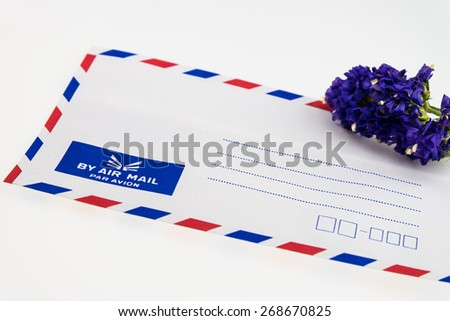 Air mail envelope and Statice flower isolated on white - stock photo