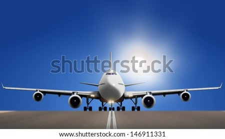 Air plane on runway with bright sun and blue sky - stock photo