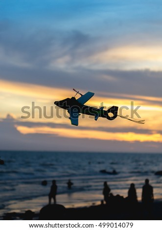 Air plane toy silhoette on the bech with sunset blur background.