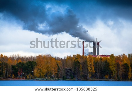 Air pollution by smoke coming out of factory chimneys - stock photo