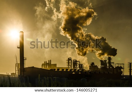 Air pollution coming from factory smoke stacks over sunset. Global concept earth preserving. Halt global warming - stock photo