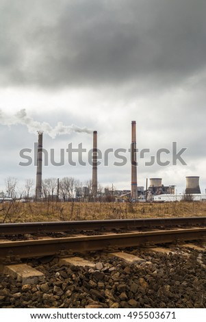 Air pollution from coal-powered plant smoke stacks, and industrial cityscape along old railroad track, on a gloomy, overcast day