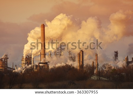 Air pollution from smoke stacks at oil refinery - stock photo