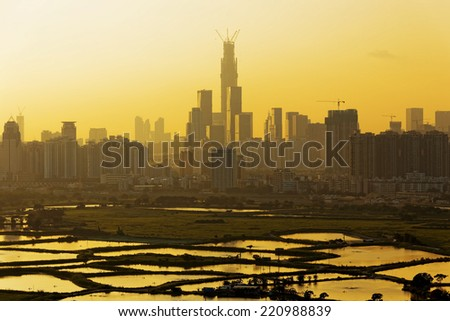 Air pollution scenic in countryside with building, rice field and yellow smoke in hong kong city at sunset - stock photo