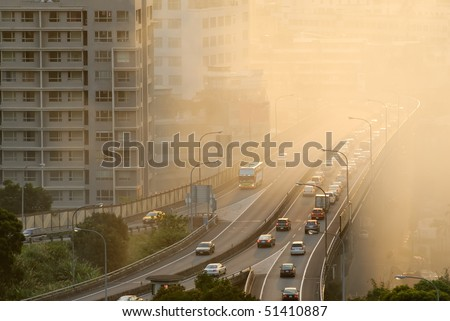 Air pollution scenic with cars on highway and yellow smoke in city. - stock photo