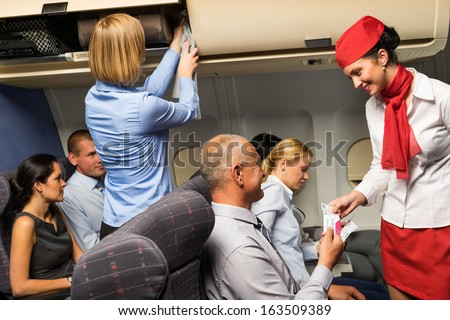 Air stewardess check passenger ticket in airplane cabin smiling - stock photo