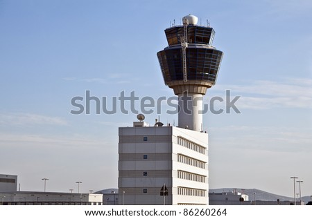 Air traffic control tower and building viewed from the ground.