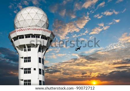 Air traffic control tower  with airplane silhouette over sunset - stock photo