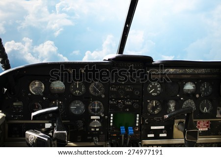 air transport, travel, technology and aviation concept - dashboard in airplane cockpit and view of cloudy sky behind windshield - stock photo