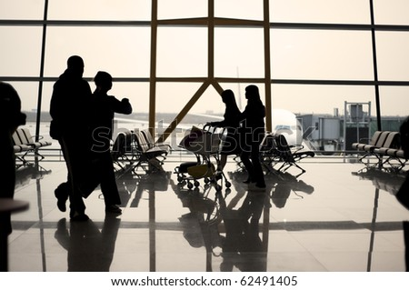 Air travellers in silhouette walking between gates at dawn - stock photo