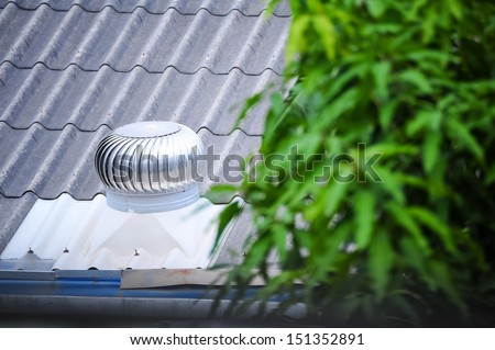 air vent on the old roof with blurred plant foreground - stock photo