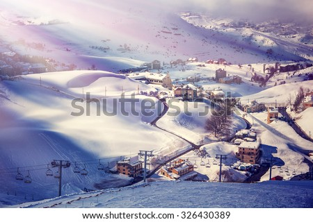 Air view on beautiful ski resort, mountain covered with snow, luxury little cottages and chalets, spending winter holidays in Lebanon - stock photo